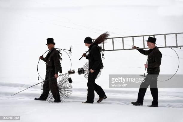 three chimney sweeps walking in snow - schornsteinfeger stock-fotos und bilder