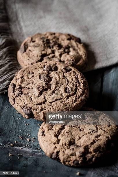 Three chocolate cookies and cloth on grey wood