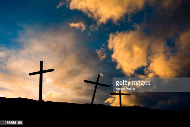 three christian crosses on a hill at sunset. religion concept - easter cross stock pictures, royalty-free photos & images