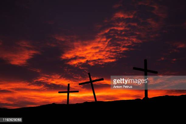 three christian crosses on a hill at sunset. religion concept - the crucifixion stock pictures, royalty-free photos & images