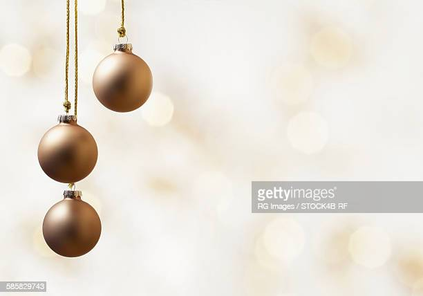 Three Christmas baubles with light background