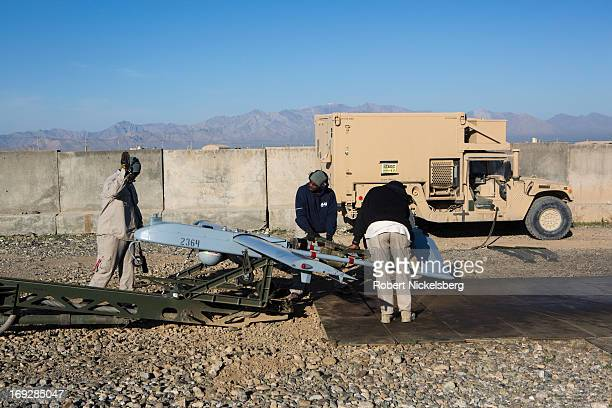 Three civilian contractors prepare a US Army 14' Shadow surveillance drone for launching at Forward Operating Base Shank May 8, 2013 in Logar...