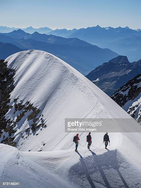 three climbers on a snowy ridge