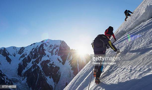 three climbers on a snowy slope