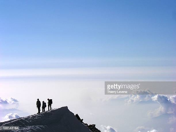three climbers on an icy ridge over the clouds - mountain ridge stock pictures, royalty-free photos & images