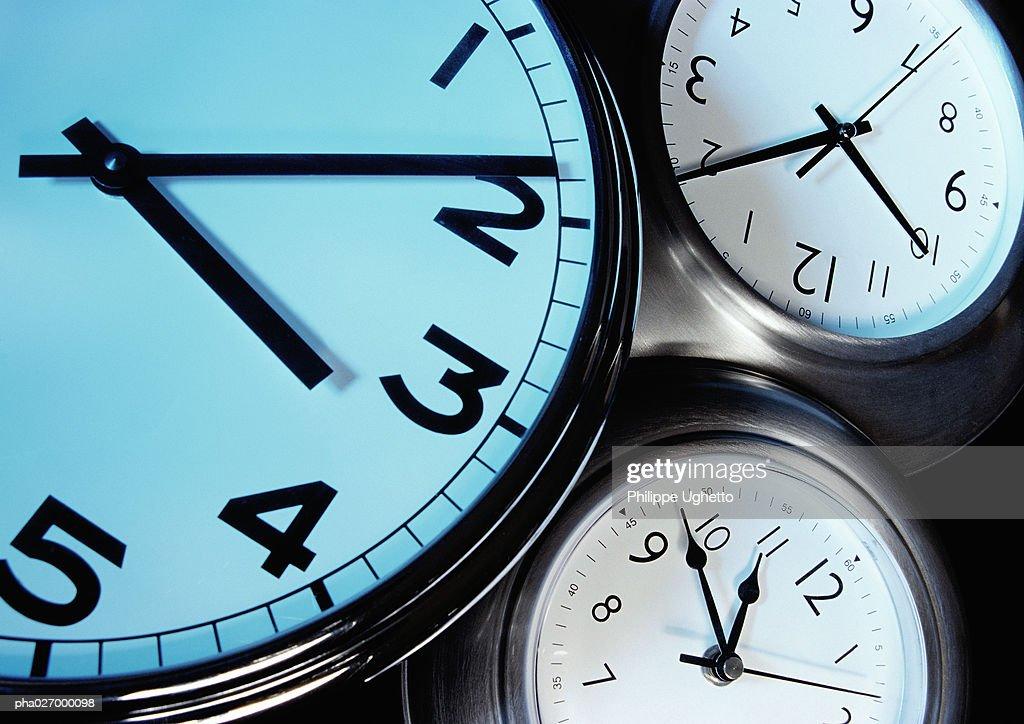 Three clocks, each with hands at a different time, extreme close-up : Stockfoto