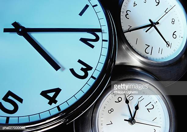 Three clocks, each with hands at a different time, extreme close-up