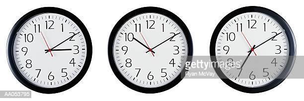 Three clocks mounted side by side