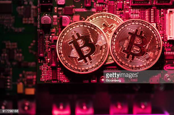 Three coins representing Bitcoin cryptocurrency sit on a computer circuit board in this arranged photograph in London UK on Tuesday Feb 6 2018...