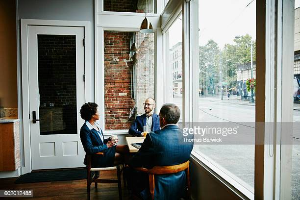 Three colleagues having informal meeting in cafe