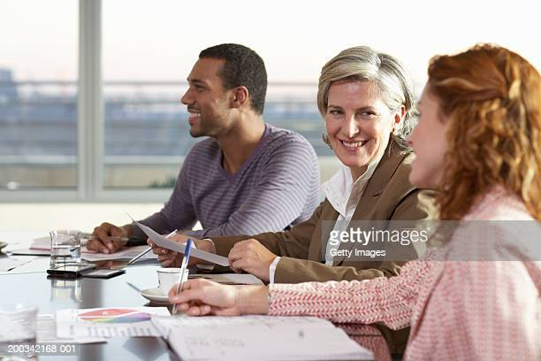 Three colleagues in business meeting, smiling