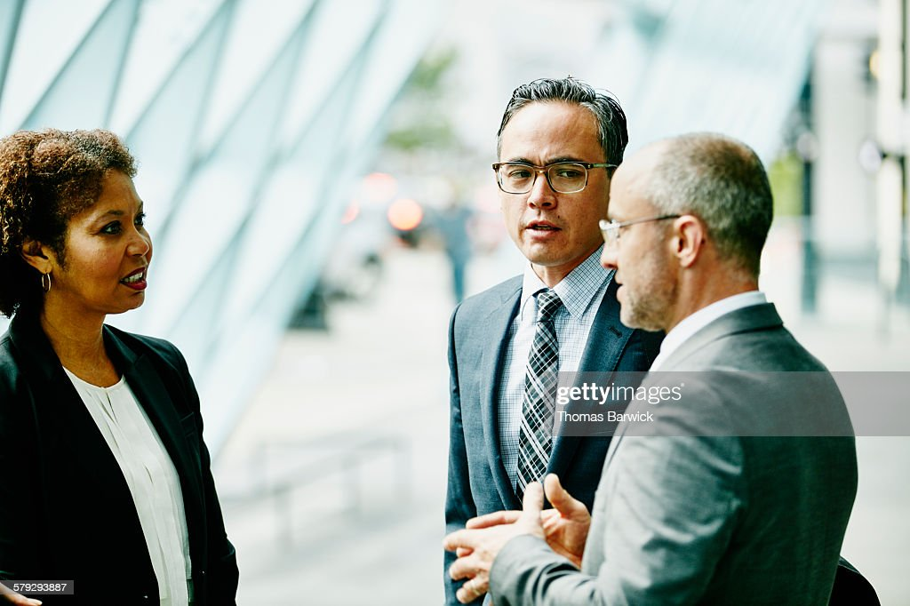 Three colleagues in discussion in corridor : Stock Photo