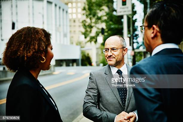 Three colleagues in discussion on sidewalk
