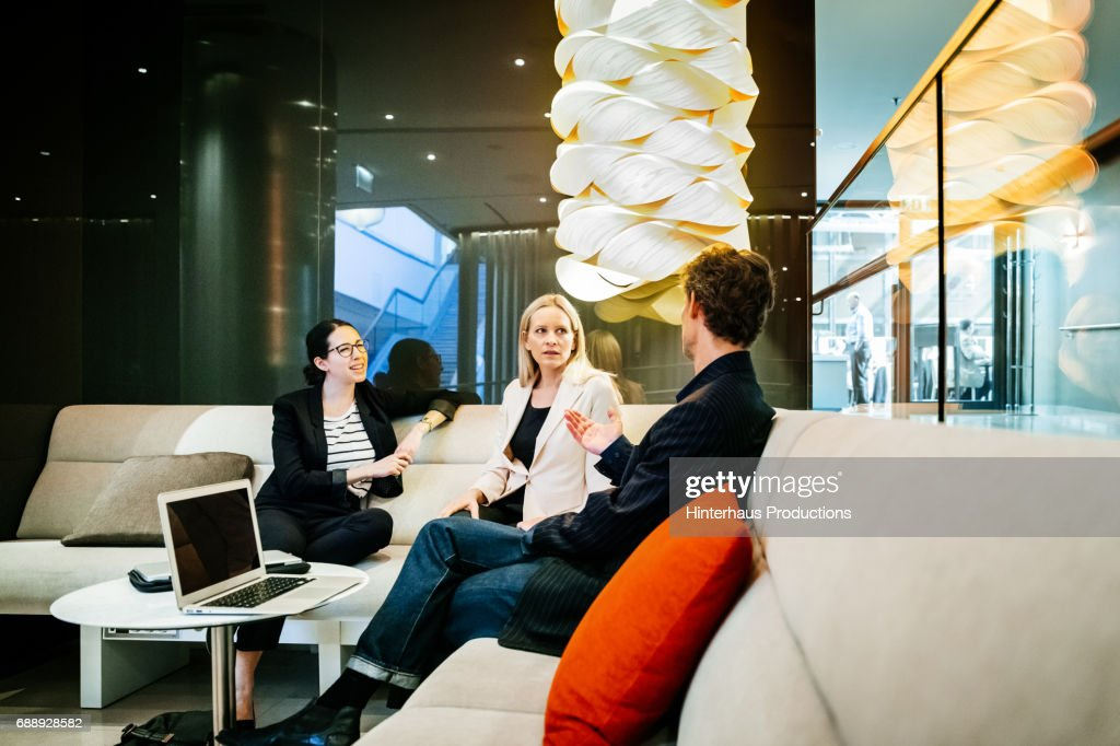 Three Colleagues Sitting In Hotel Foyer Discussing A Project : Stock Photo