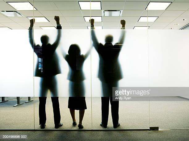Three colleagues standing behind frosted glass in office, arms up