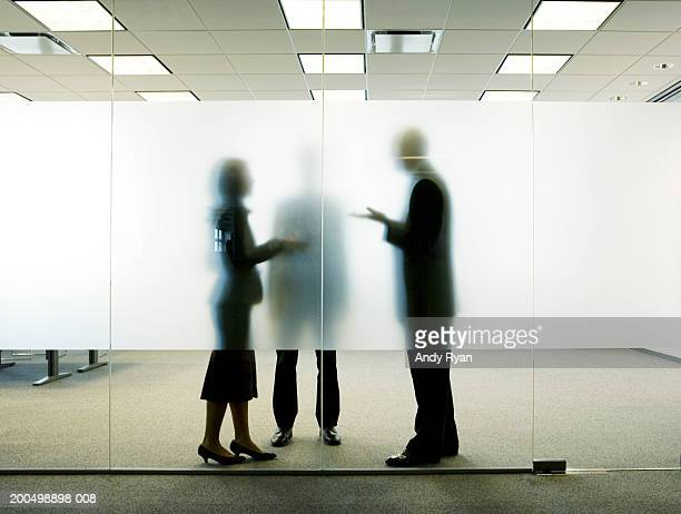 Three colleagues standing behind frosted glass in office, talking