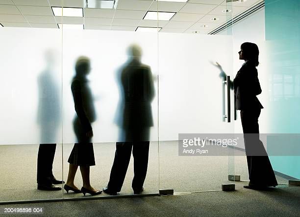 Three colleagues standing behind frosted glass, woman entering office