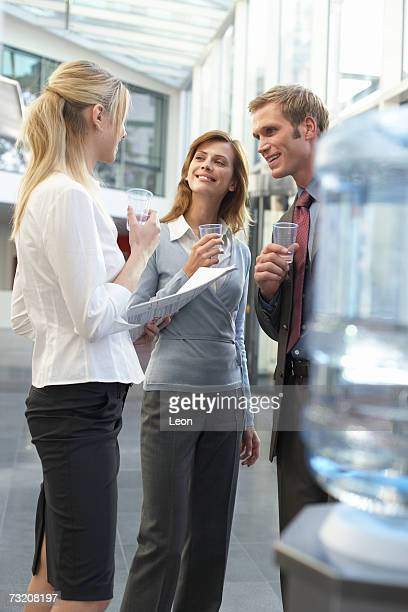 Three colleagues talking by water cooler in office