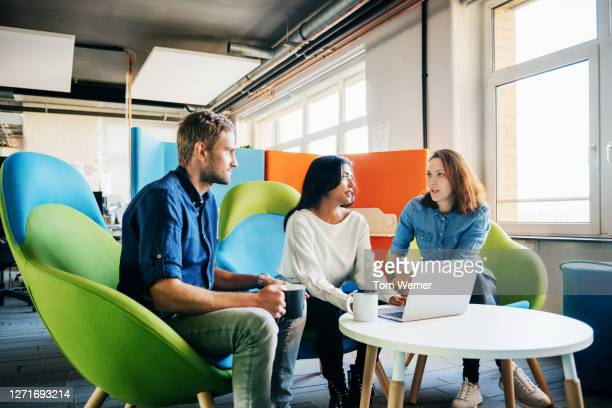 three colleagues talking during meeting in office - three people stock pictures, royalty-free photos & images