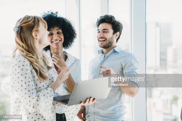 três colegas trabalhando juntos com um laptop - new business - fotografias e filmes do acervo