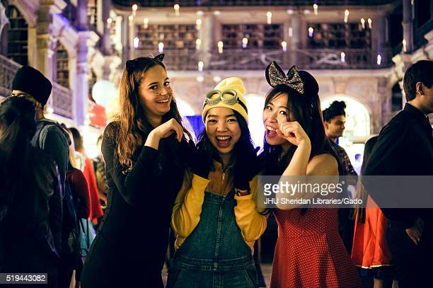 Three college students in costume pose for a photo the girl on the far left is dressed as a black cat the girl in the middle is dressed as a minion...