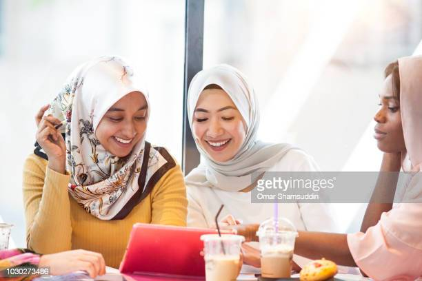 Three college students in hijab are studying using the tablet