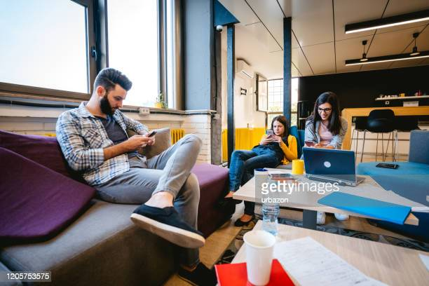 three college students using phones - unity stock pictures, royalty-free photos & images