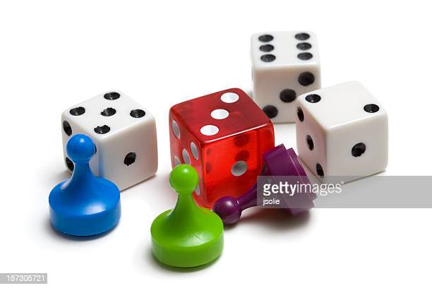 Three colored game pieces and four dice on white background