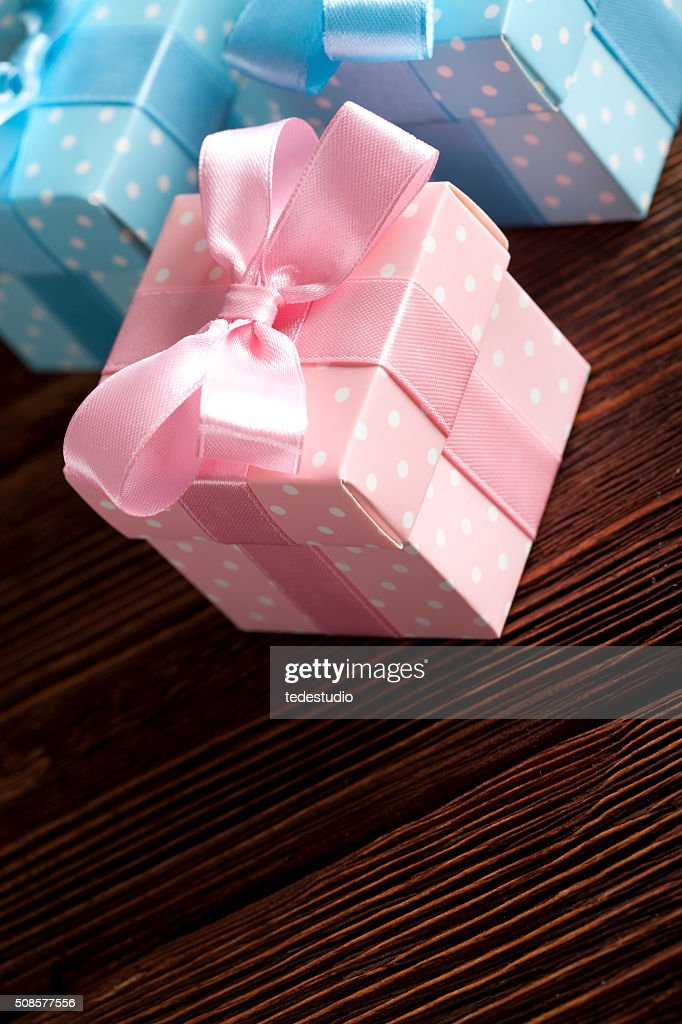 Three colored gift boxes on wooden background : Stock Photo