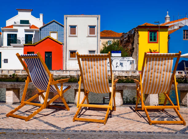 Three colorful deckchairs on a sunny day in front of the houses of the Beira-Mar neighborhood, Aveiro, Portugal