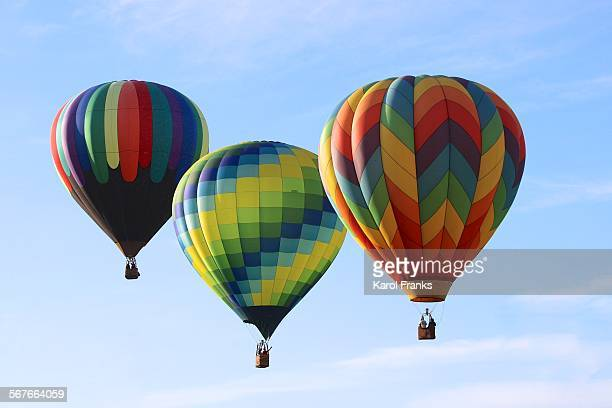three colorful hot air balloons in the sky - balloon fiesta stock pictures, royalty-free photos & images