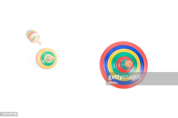 Three colorful spinning gyroscopes, taken from above.