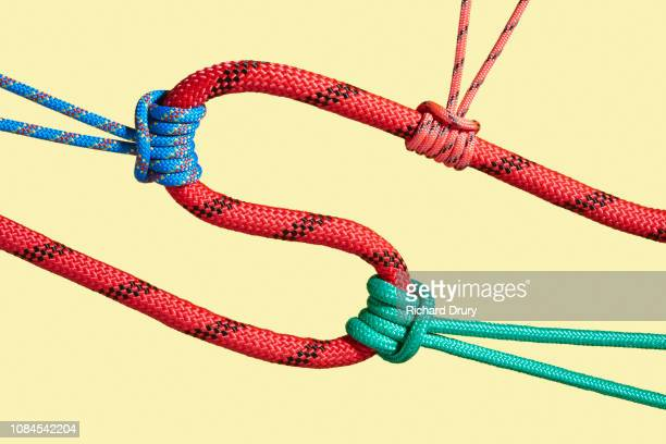 three coloured ropes pulling on a larger rope to shape its path - befestigen stock-fotos und bilder
