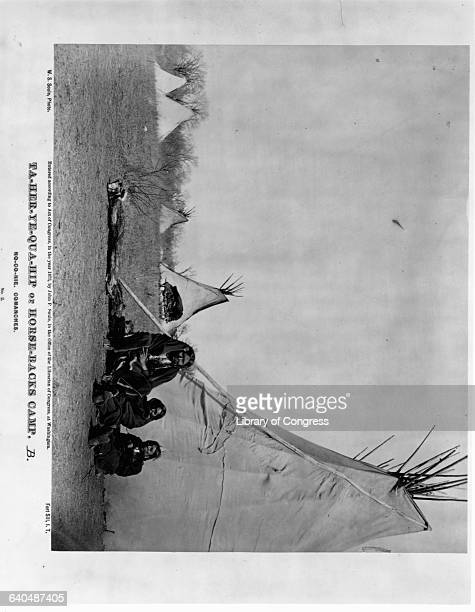 Three Comanche Indians relax in front of a tepee at HorseBack's Camp TaHerYeQuaHip