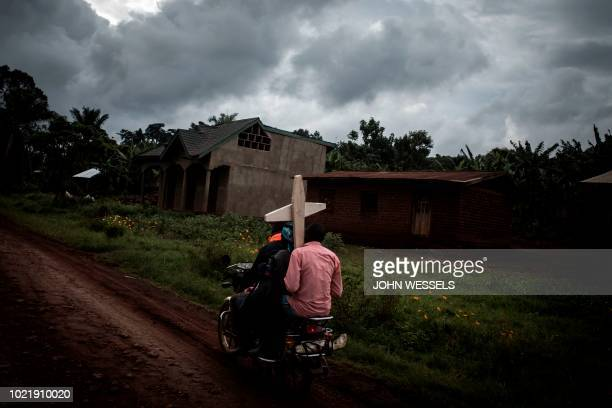 Three Congolese ride a motorbike and carry a cross for a grave along the road linking Mangina to Beni on August 23, 2018 in Mangina, in the North...