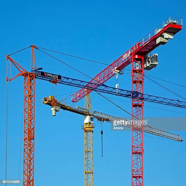 Three construction cranes / tower crane against blue sky