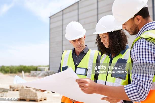 three construction engineers discussing building plans on a worksite - real estate developer stock pictures, royalty-free photos & images