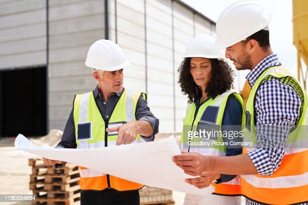 three construction engineers going over building plans on a worksite - real estate developer stock pictures, royalty-free photos & images