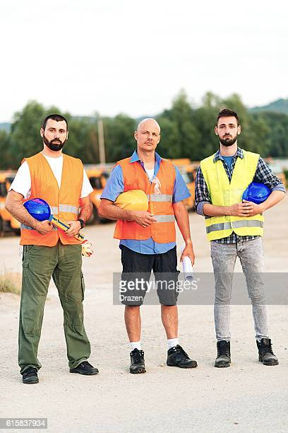 Three construction workers or engineers on construction site