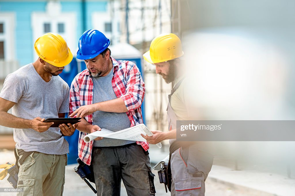 Three construction workers preparing for work : Stock Photo