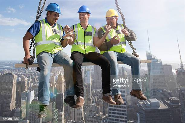 Three construction workers sitting on suspended scaffolding high above city having lunch