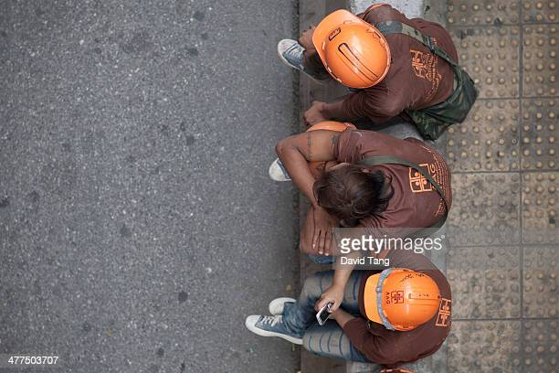 CONTENT] Three construction workers take a break on the streets of Bangkok Thailand