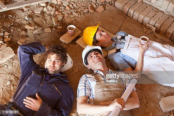 Three construction workers taking a coffee break