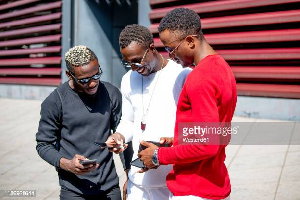 three cool young men using cell phones in the city - segnale informativo foto e immagini stock