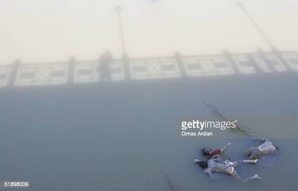 Three corpses float in a river after a Tsunami hit the Indonesian City of Banda Aceh 150 miles from southern Asia's massive earthquake's epicentre...