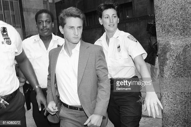 Three court officers escort actor Sean Penn to his arraignment on charges of attacking a New York Post photographer's car