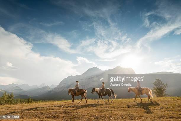 Three cowboys/cowgirls lead horses thru mountains