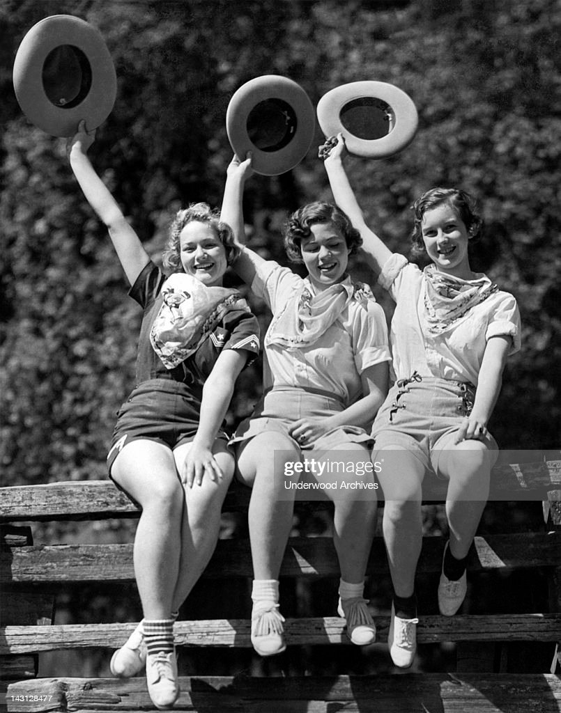 Three cowgirls on a corral fence are ready for the Frontier Days celebration held over the Fourth of July, Willits, California, 1936.