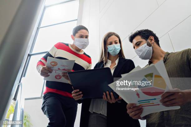 three coworkers are on the stairs of the company where they work with graphic documents and laptop all three wear masks - graphic accident photos stock pictures, royalty-free photos & images