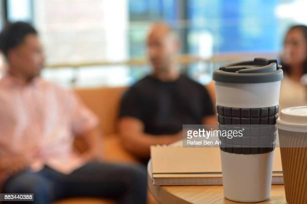 three co-workers having having a coffee break - rafael ben ari stock-fotos und bilder